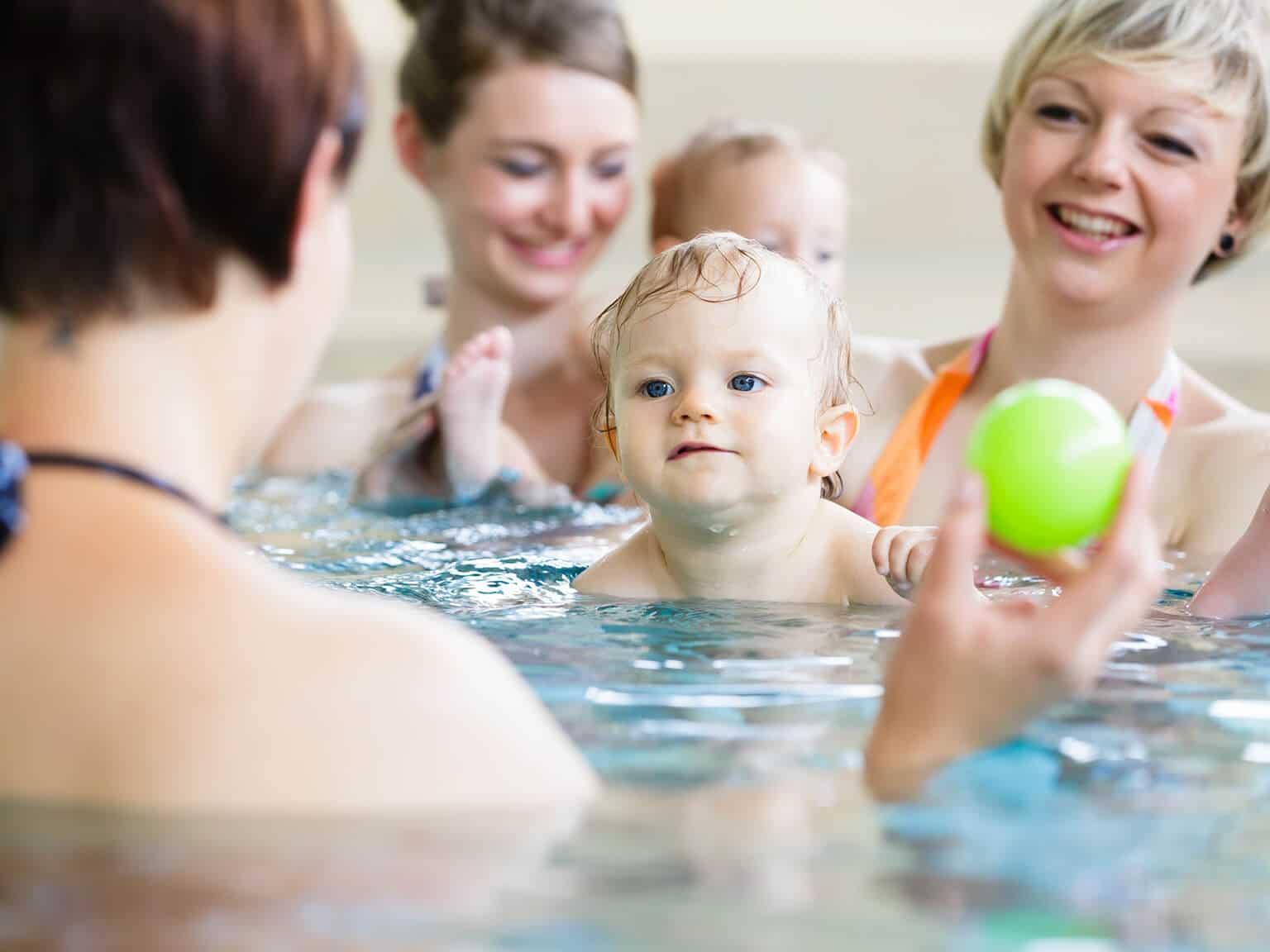 Kinder und Mütter beim Kleinkinderschwimmen