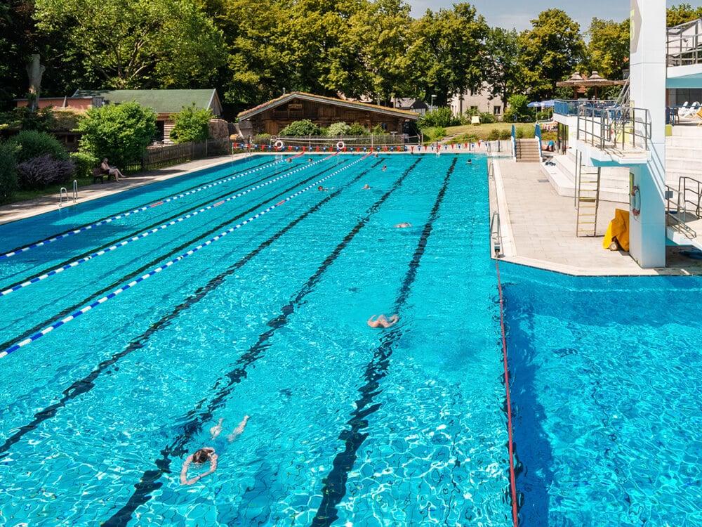 Blick auf eine Wasserfläche mit Schwimmbahnen, im Hintergrund eine Saunahütte