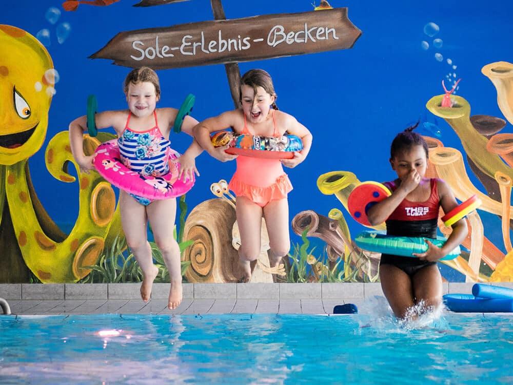 Drei Mädchen mit Schwimmreifen springen ins Wasser